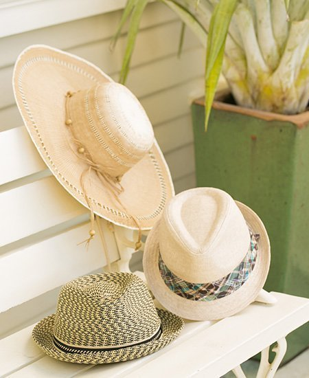 three beige weave hats from Chapel Hats Sheraton Waikiki. one broad sunbrim, and two bowler hats on a wooden bench.