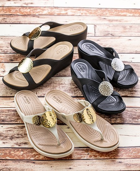 three pairs of Crocs sandals and wedges in black, beige, and white