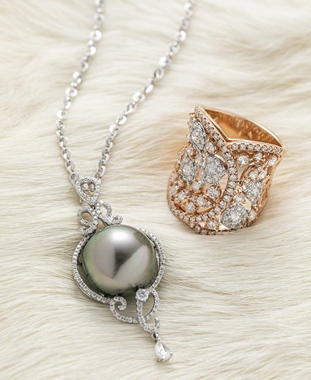 Tahitian Pearl pendant next to a Rose Gold ring inset with diamonds
