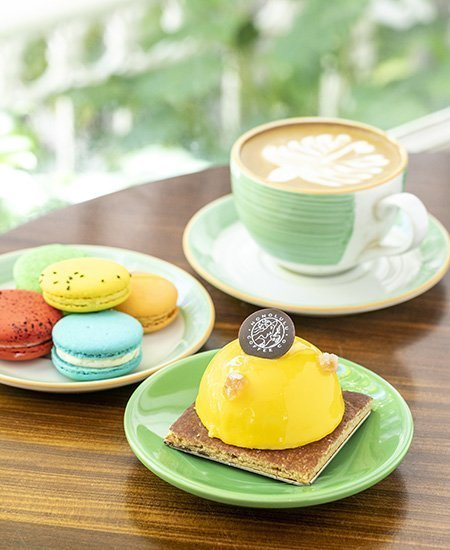 hot latte with leaf latte art, a plate of colorful macarons, and a mango dessert, all by Honolulu Coffee at the Moana Surfrider