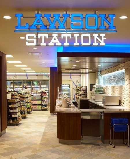 interior photo of the Lawson Station convenience store, showing the register area and logo
