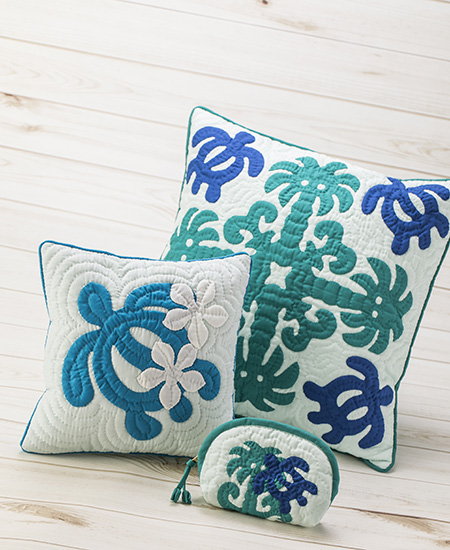 two blue, green, and white quilted Hawaiian pillows with turtle motifs by Moana Quilts