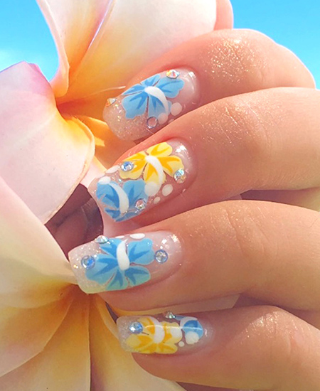 yellow and blue plumeria flower nail art by Naillabo on a female model