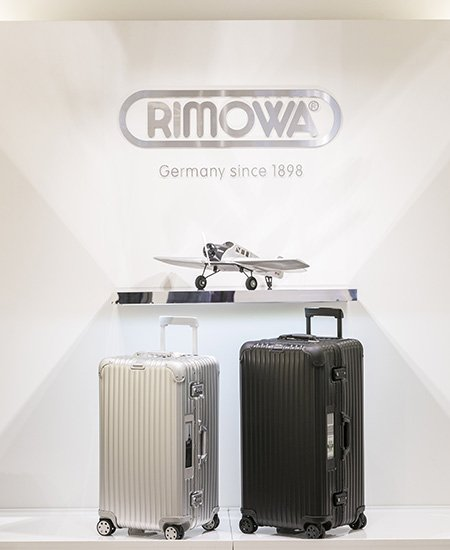 two Rimowa sleek-looking suitcases at the Moana Surfrider, one silver, and one black