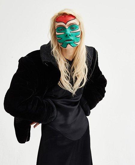 face-painted model wearing black Vivienne Westwood overcoat and sleek black dress