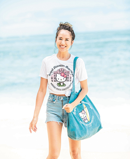 female model wearing a Royal Hawaiian x Hello Kitty collaboration white t-shirt and also holding a Hello Kitty collab demin bag