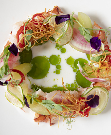 slices of lime, radish, peppers, and other seasonal vegetables arranged in a circular wreath on a plate