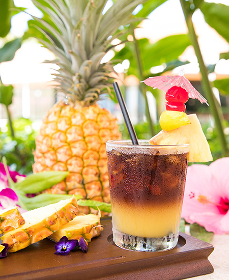 a delicious-looking Mai Tai with pineapple and pineapple slices in the background at the Mai Tai Bar