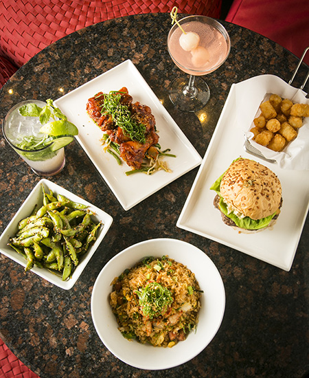 top down photo of an arrangement of food at RumFire, from burgers and tater tots, to BBQ chicken wings, edamane, and cocktails