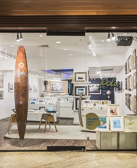 photo of the exterior of the Polu Gallery store, showing a wide variety of surf art