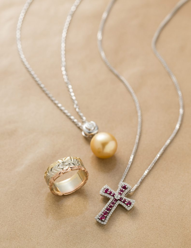 Tri-color Hawaiian ring, white pearl necklace, and jeweled cross necklace